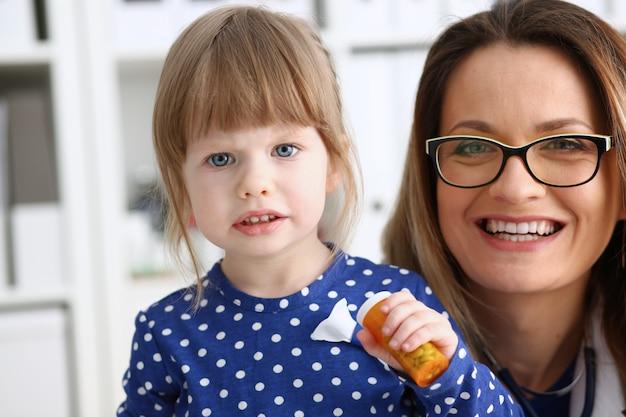 Klein kind met moeder bij kinderarts receptie