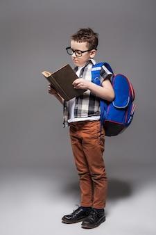 Klein kind met schooltas en boek
