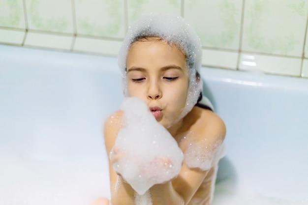 Klein kind nemen van een bad met schuim