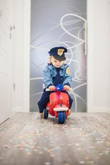 Klein kind op een rode scooter gekleed als een politieagent