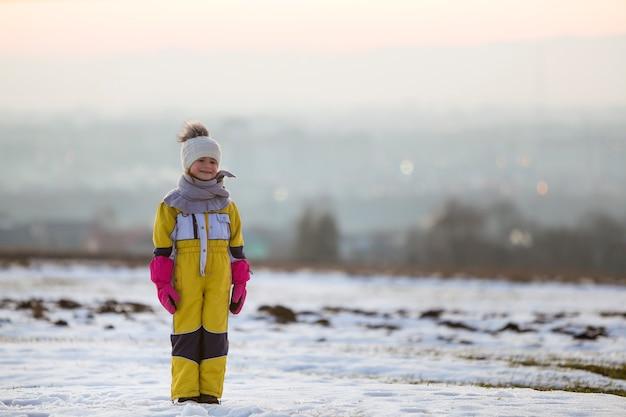 Klein kind permanent buiten op sneeuw bedekt veld