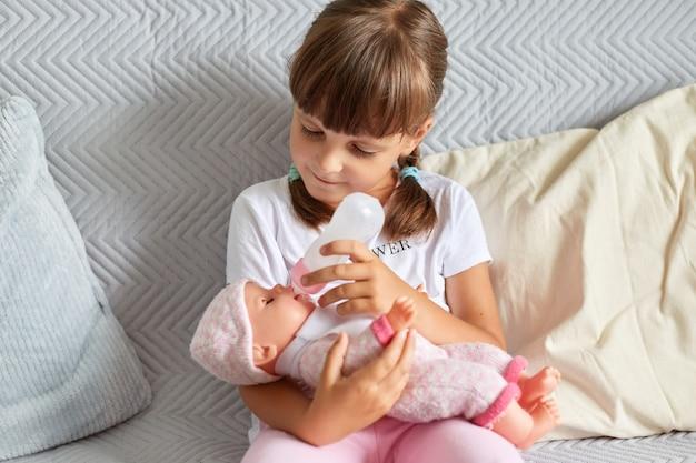 Klein kind, schattig donkerharig peutermeisje dat haar pop voedt die binnenshuis speelt, op de bank zit met kussens, favoriete speelgoed in handen houdt, kindertijd.