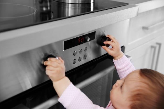 Klein kind spelen met elektrisch fornuis in de keuken