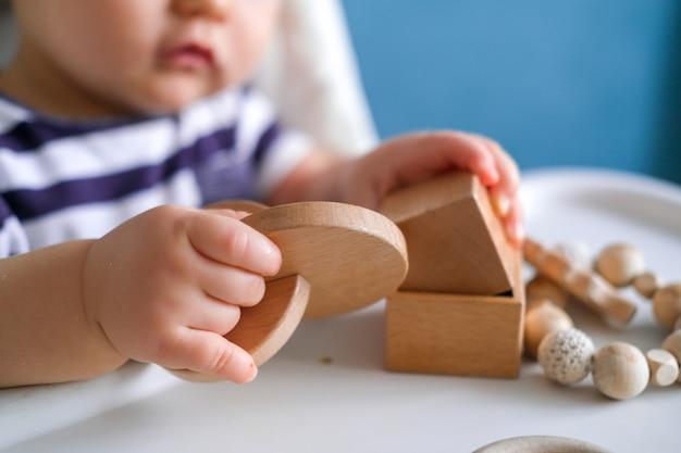 Klein kind spelen met houten speelgoed op kinderstoel