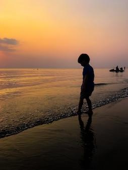 Klein kind spelen op een zandstrand silhouet