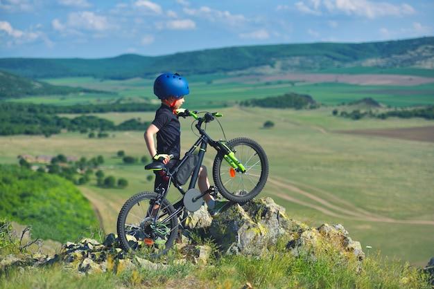 Klein kind staat naast zijn mountainbike op de rand van de bergen en kijkt naar het prachtige landschap