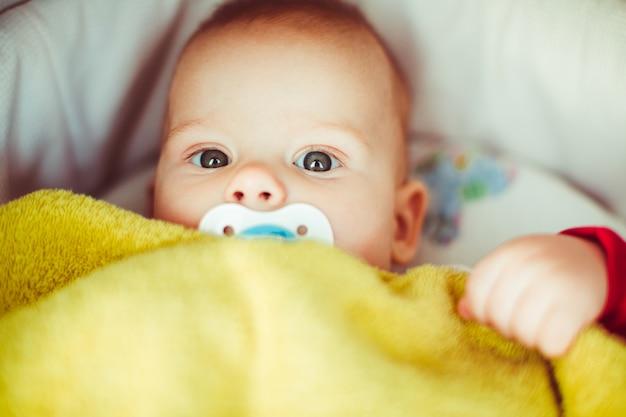 Klein kind verborgen onder gele deken