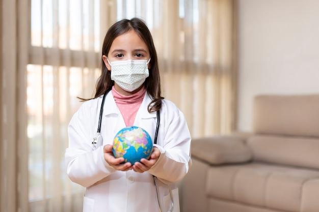 Klein kind verkleed als arts met een medisch masker met een bal van de wereld in haar handen