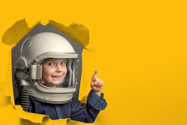 Klein kind wil een vliegtuig besturen dat een vliegtuighelm draagt