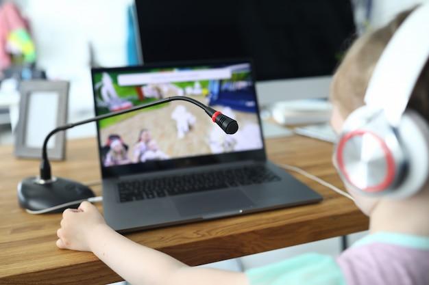 Klein kind zit aan tafel en kijkt naar laptop scherm