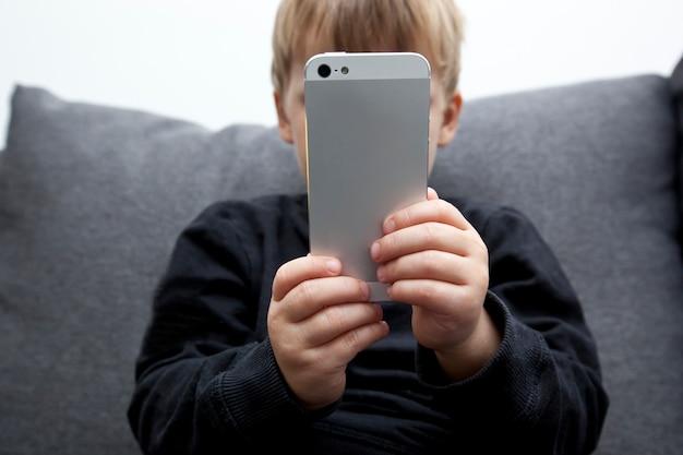 Klein kind zit alleen op de bank en kijkt in zijn telefoon