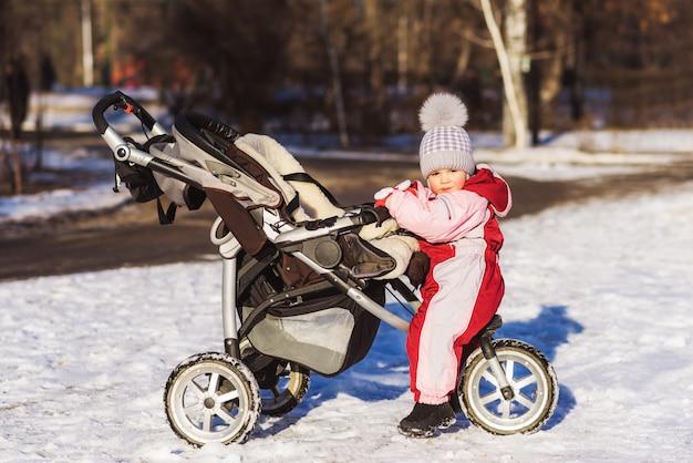 Klein kind zit in een kinderwagen in de winter