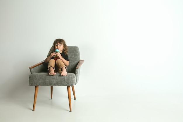 Klein kind zitten en spelen in fauteuil geïsoleerd op witte ruimte. een jonge jongen met blond haar kijkt geïnteresseerd in de wereld om hem heen