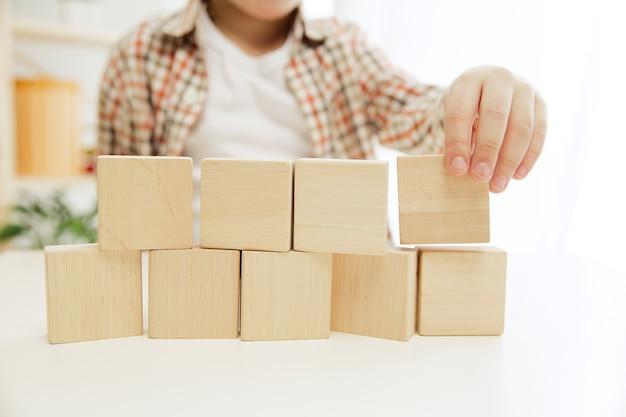 Klein kind zittend op de vloer. mooie jongen die thuis met houten kubussen palying.