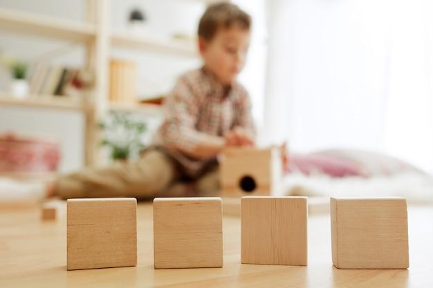 Klein kind zittend op de vloer. mooie jongen die thuis met houten kubussen speelt. conceptuele afbeelding met kopie of negatieve ruimte