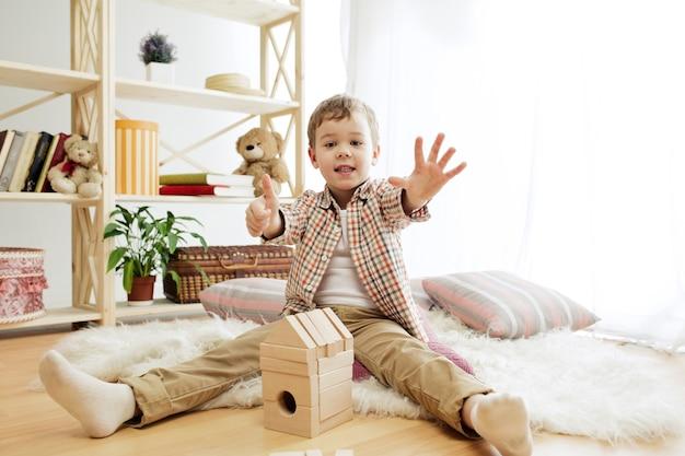 Klein kind zittend op de vloer. mooie jongen die thuis met houten kubussen speelt.