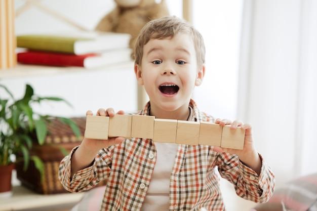 Klein kind zittend op de vloer. vrij lachende verrast jongen spelen met houten kubussen thuis. .