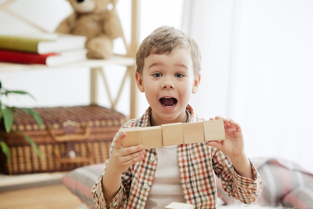 Klein kind zittend op de vloer. vrij lachende verraste jongen die thuis met houten kubussen speelt. conceptuele afbeelding met kopie of negatieve ruimte en mock-up voor uw tekst.