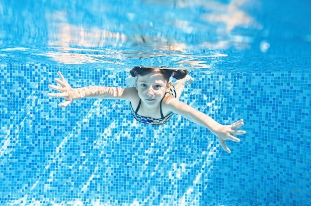 Klein kind zwemt onder water in zwembad, gelukkig actief meisje duikt en heeft plezier onder water, kindfitness en sport