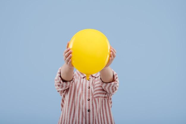 Klein kindmeisje dat gezicht bedekt met gele ballon, gekleed in gestreept shirt, geïsoleerd op blauwe achtergrond, kopieer ruimte