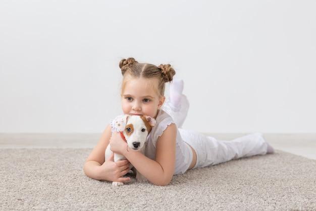 Klein kindmeisje dat op de vloer met leuke puppy jack ligt