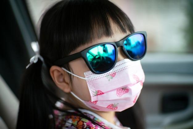 Klein kindmeisje dat zonnebril en gezichtsmasker draagt om corona-virus of covid-19 in de auto te verhinderen