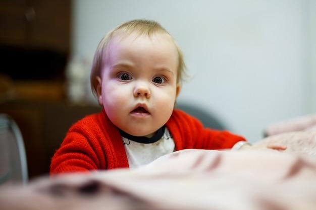 Klein kindmeisje in een rode trui, haar gezicht is vies van eten, mooie bokeh