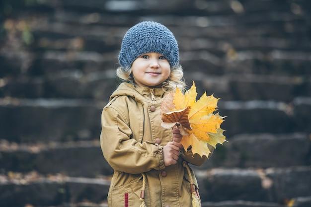 Klein kindmeisje in warme jas en hoed in de herfst in het park