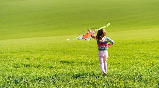 Klein kindmeisje loopt met vlieger op het veld met groen gras