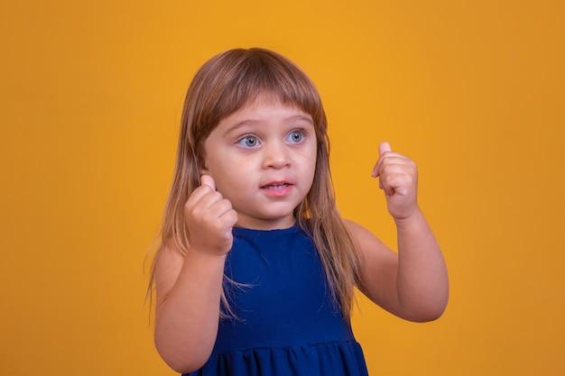 Klein kindmeisje met omhoog duim. klein meisje dat de duimen opgeeft met haar hand