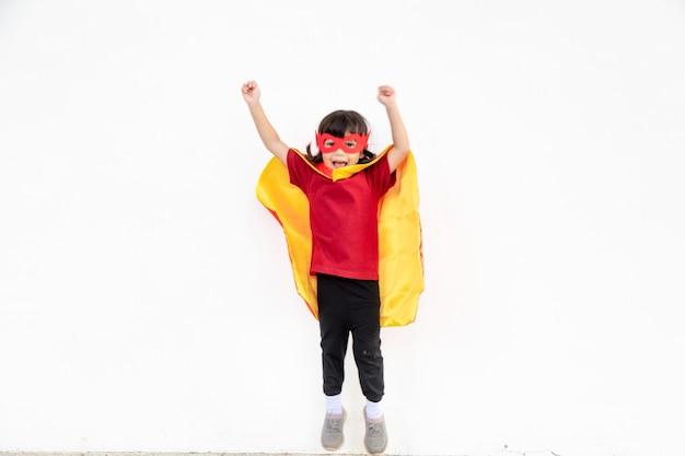 Klein kindmeisje speelt superheld. kind op de witte achtergrond. girl power-concept
