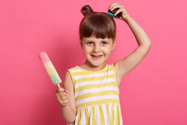 Klein klein kind met charmante glimlach, haarbroodje, gekleed geel en wit gestreepte sarafan, kijkt naar de camera, poses geïsoleerd op roze achtergrond, haar knoop aan te raken.