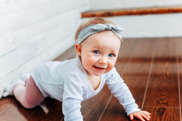Klein kruipend babymeisje van een jaar oud dat op de vloer zit in een fel lichte woonkamer bij het raam glimlachend en lachend. gelukkig peuter kind thuis spelen. jeugd concept