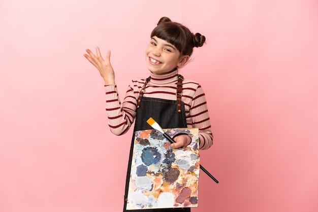 Klein kunstenaarsmeisje dat een palet houdt dat op roze muur wordt geïsoleerd die handen naar de kant uitbreidt om uit te nodigen om te komen