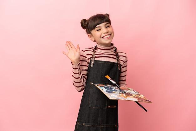 Klein kunstenaarsmeisje die een palet houden dat op roze muur wordt geïsoleerd die met hand met gelukkige uitdrukking groeten