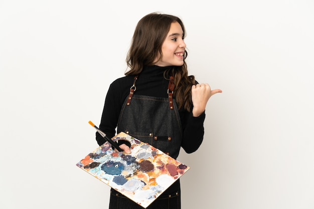 Klein kunstenaarsmeisje die een palet houden dat op witte muur wordt geïsoleerd die naar de kant wijst om een product te presenteren