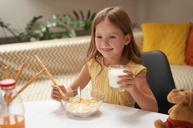 Klein lachend kaukasisch meisje dat melk drinkt en ontbijtgranen eet terwijl ze thuis ontbijt