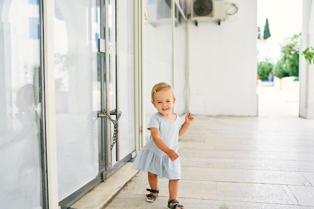 Klein lachend meisje dat op de tegels loopt bij de glazen deur van het huis