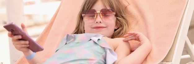 Klein lachend meisje in zonnebril ligt op een ligstoel met smartphone in haar handen