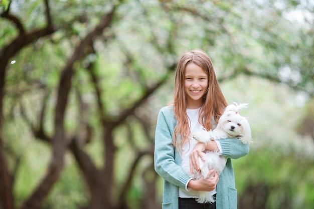 Klein lachend meisje spelen en knuffelen puppy in het park