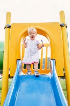 Klein lachend meisje staat op de top van de glijbaan op de speelplaats