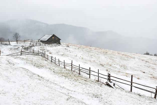Klein landelijk huis in de witte winterbergen