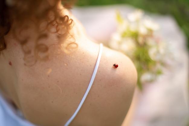 Klein lieveheersbeestje zit op de schouder van een jonge vrouw
