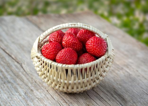 Klein mandje vol aardbeien op oude houten plank