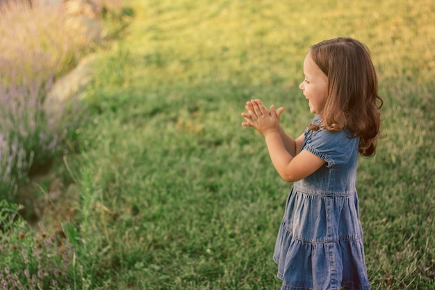 Klein meisje 3-4 met donker haar in denim jurk klapt en lacht, staande op groen gazon