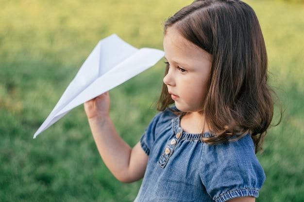 Klein meisje 3-4 met donker haar in spijkerjurk in de zon lanceert papieren vliegtuig, staande op groen gazon