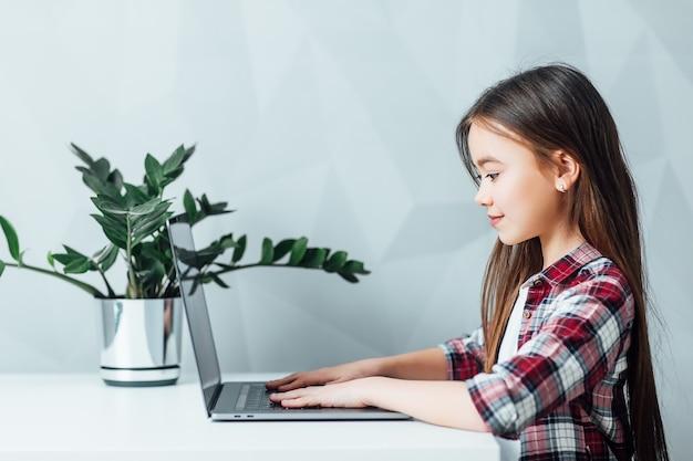 Klein meisje aan tafel zitten en moderne tablet gebruiken