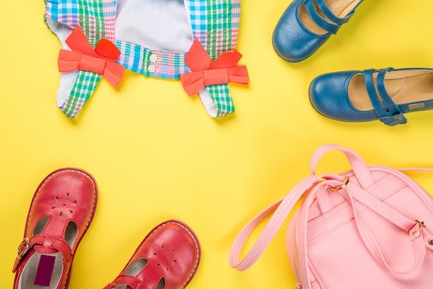 Klein meisje accessoires. roze tas met kleurrijke jurk en schoenen op gele ondergrond.