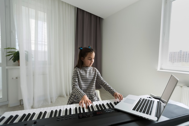 Klein meisje afstand leren van de piano online tijdens quarantaine. coronavirus concept.