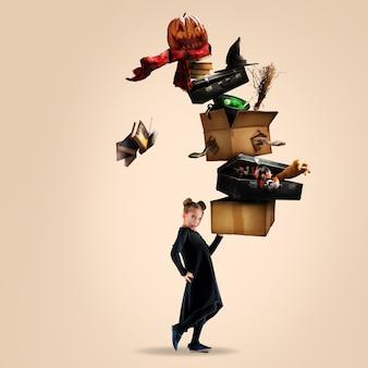 Klein meisje als een vampier op zift bruine achtergrond met doos met slangen, boeken, pompoen, heksenuitrusting. zwarte vrijdag, verkoop, concept. kopieerruimte. halloween, allerheiligenstemming, oktober.